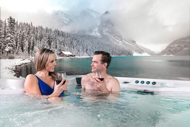 A couple drinking in a hot tub.