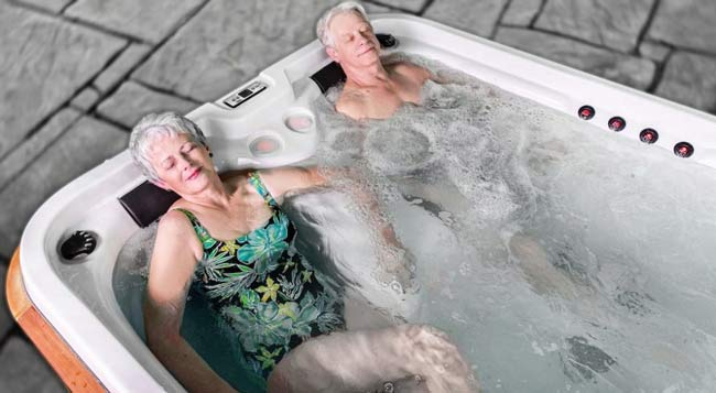 An elderly couple relaxing in a hot tub.