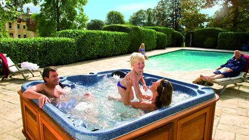 A couple having fun with a toddler in a hot tub