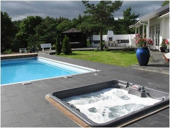 hot tub next to the swimming pool in the garden