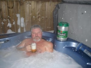 Pat drinking a beer in a hot tub in winter