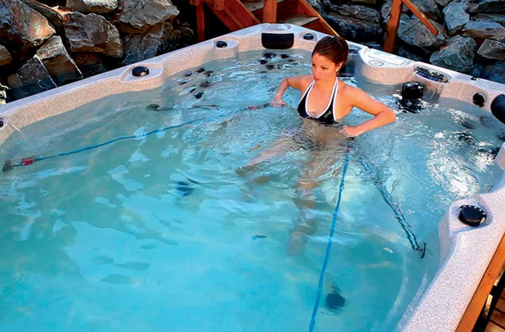 A woman rowing in the swim spa