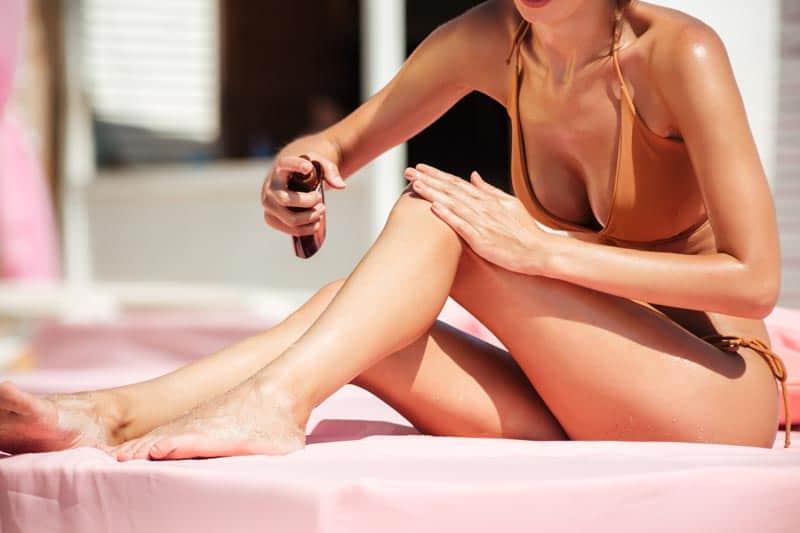 A woman applies sunscreen on her legs